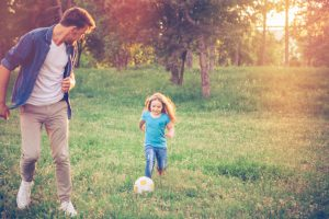 Young father playing soccer ball with daughter at a park. Sun flare, green grass, summer time. Caucasian, blond hair.